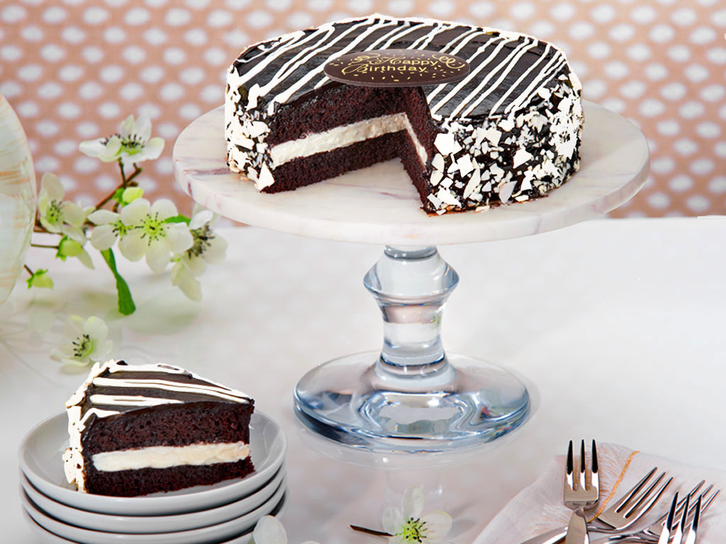 This delicious fusion of flavor will make your taste buds explode! This decadent, two-layered chocolate cake is filled with a mixture of whipped buttercream and chocolate cream, and then coated in a thick layer of dark chocolate fudge frosting-talk about icing on the cake! For the final, decorative touch, the cake is then embellished with white chocolate drizzles and shavings. This delectable cake is delivered with a chocolate plaque as well as a matching greeting card, defining your loved ones occasion. Order online for nationwide delivery!